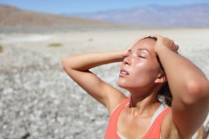 Desert woman thirsty dehydrated in Death Valley. Dehydration, overheating, thirst and heat stroke concept image with girl in desert nature.